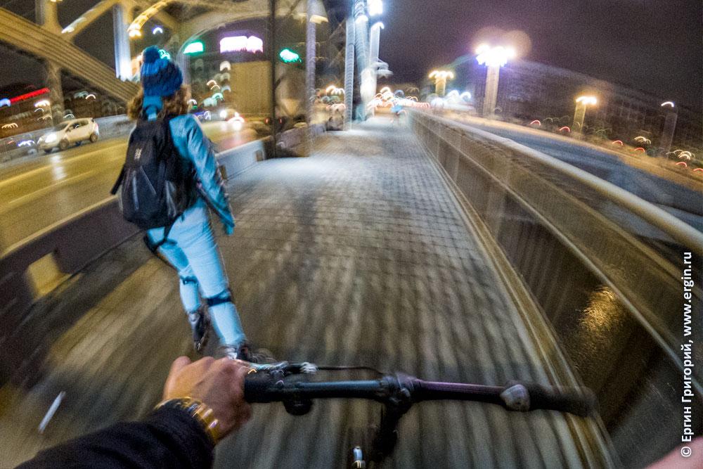 Велосипедист едет за роллером по Большеохтинскому мосту