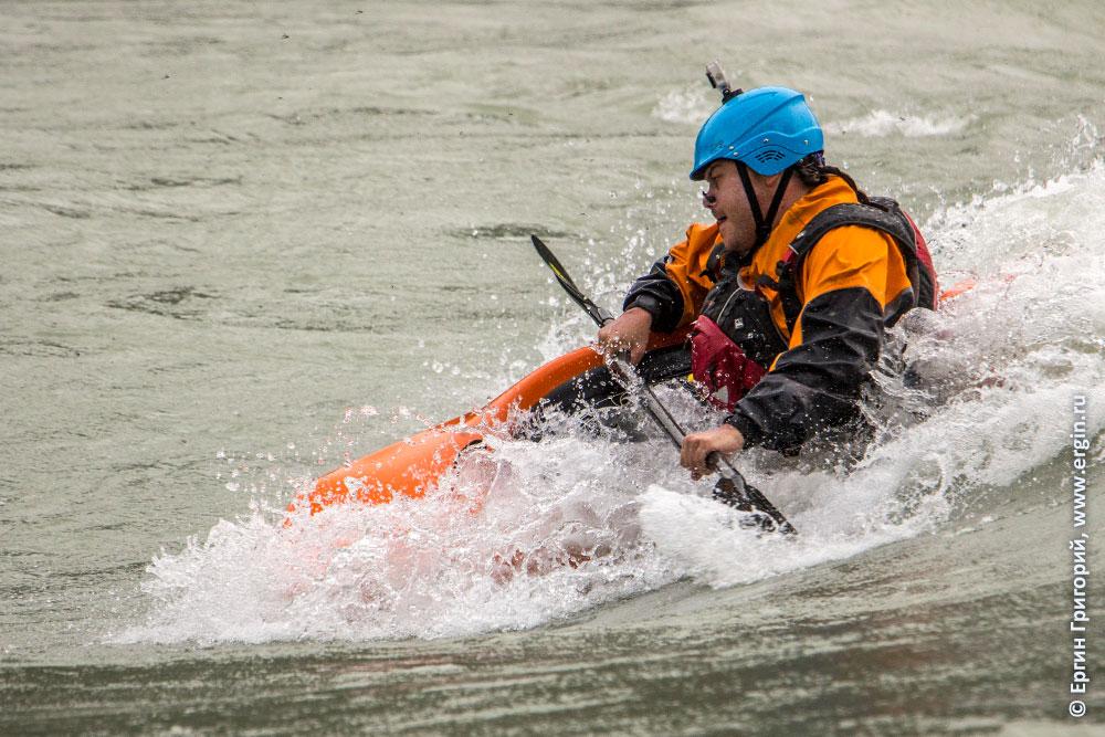 Каякер фристайлер старательно катается на бурной воде