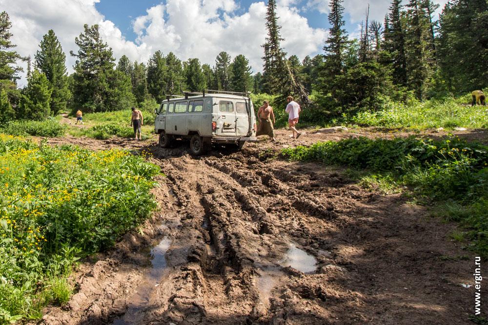 УАЗик буханка едет по разбитой дороге бездорожью в горах перевал