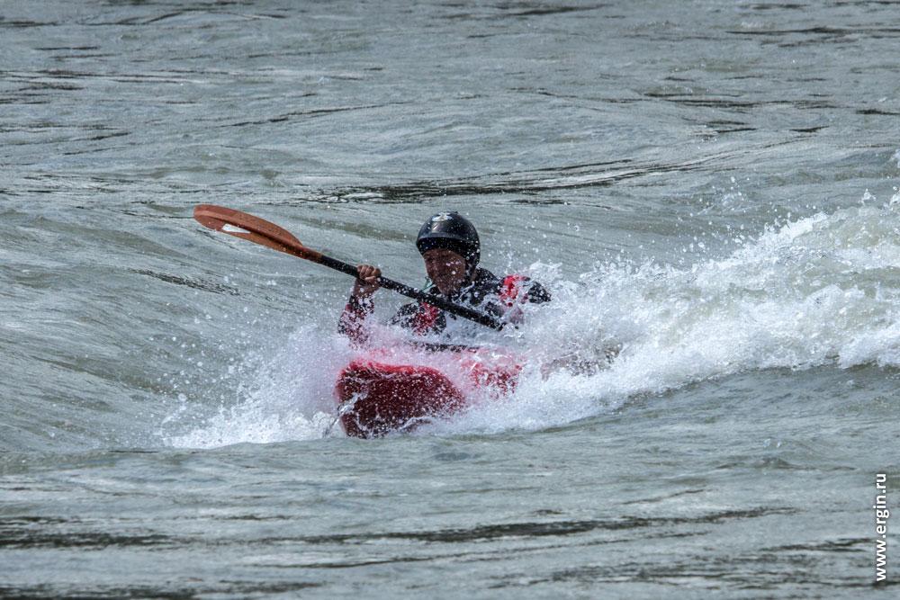 Каякер девушка улыбается в пороге в каяке на бурной воде