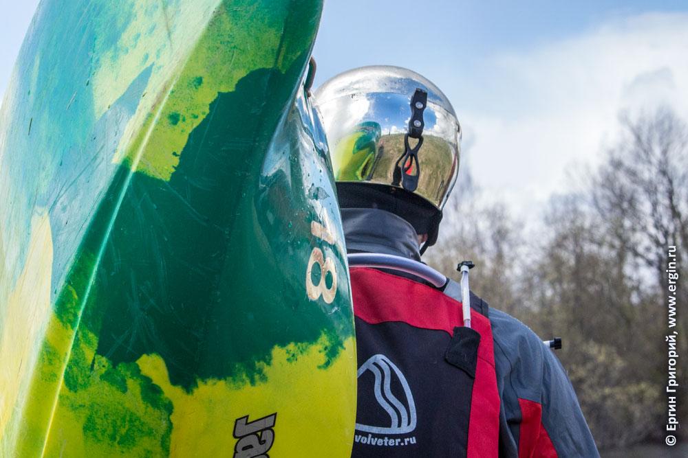 Каякер с зеркальным шлемом и каяком на берегу реки