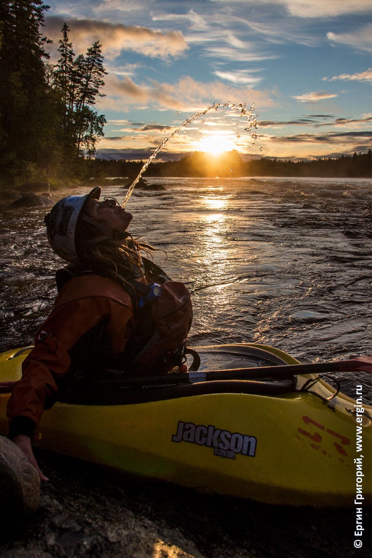Девущка каякер пускает струйку воды над закатным солнцем в Лиексе
