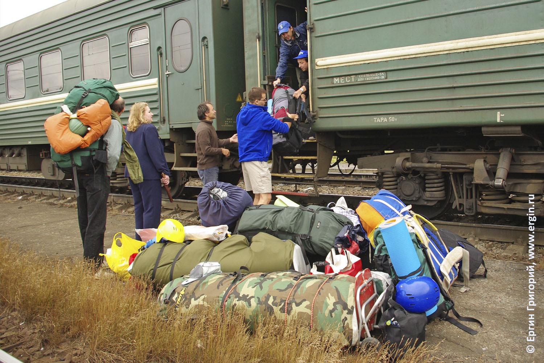 Байдарочники разгружают вещи из поезда байдарки палатки