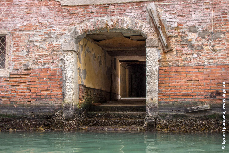 Заросшие водорослями ступеньки входа в арку дома в Венеции