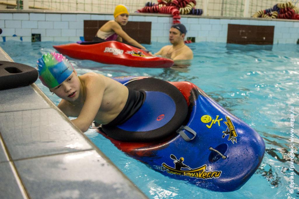 Ребенок тренируется эскимосский переворот на каяке в бассейне