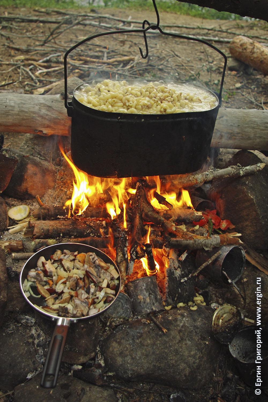 На костре готовится еда в походе котел котелок огонь макароны