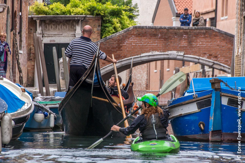 Каякер и асимметричная гондола на канале в Венеции