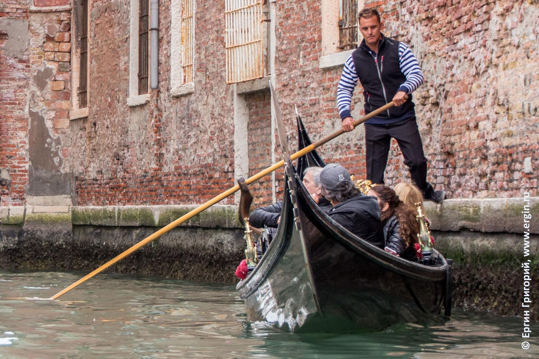 Гондольер управляет гондолой, отталкиваясь от стены здания в Венеции