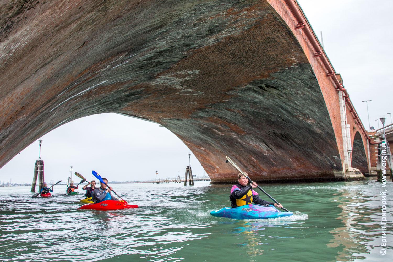 Каякеры проходят под мостом делла Либерта в Венеции, который соединяет город с материковой частью Италии