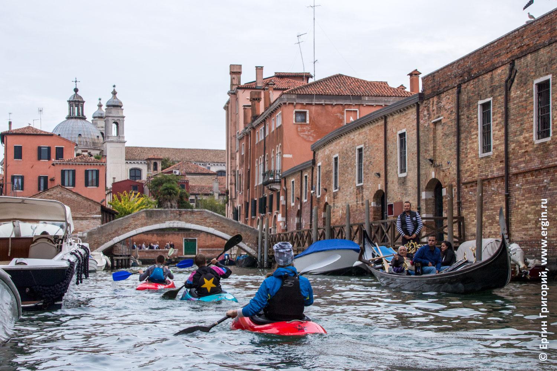 Каякеры плывут мимо гондольеров в Венеции
