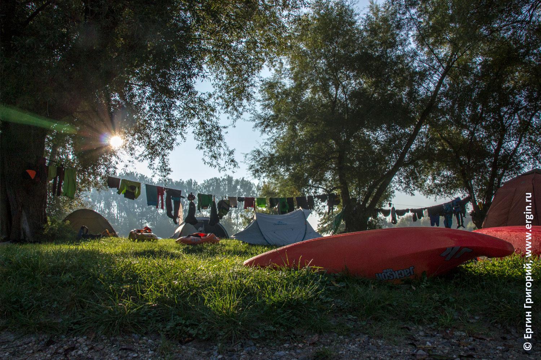 Утреннее солнце из-за деревьев каяки и лагерь каякеров