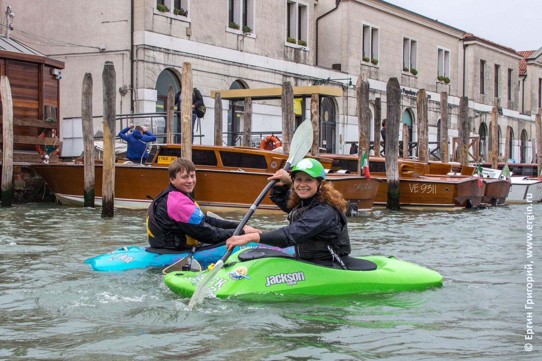 Каякеры на фоне автостоянки катеров моторных лодок в Венеции