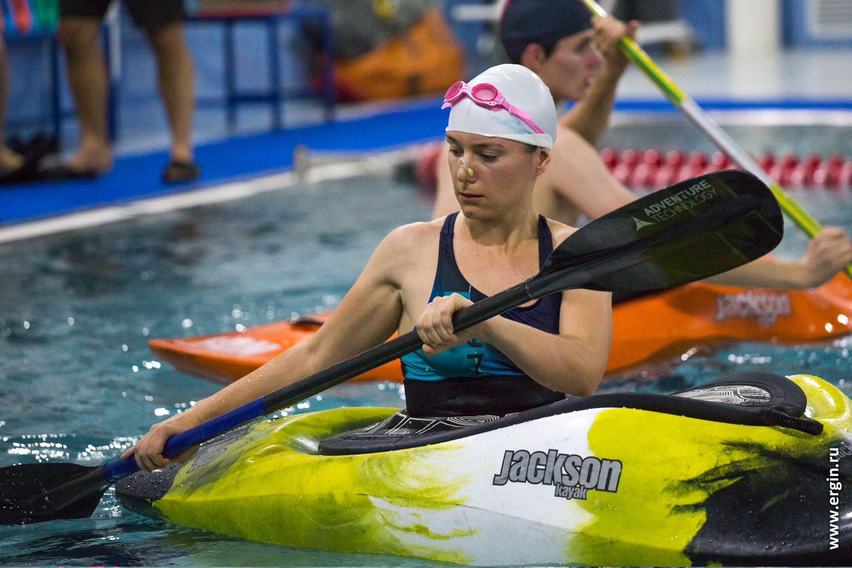 Девушка каякер гребет на каяке в бассейне с веслом