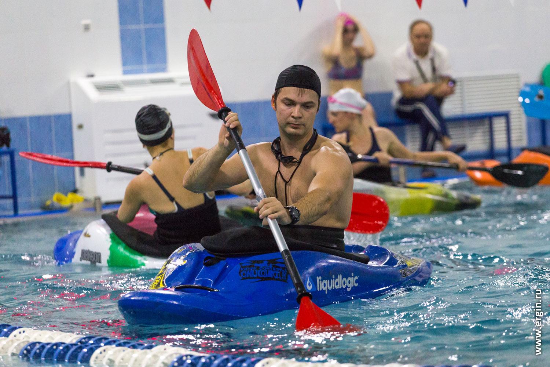 На каяке с веслом в бассейне каякер гребет