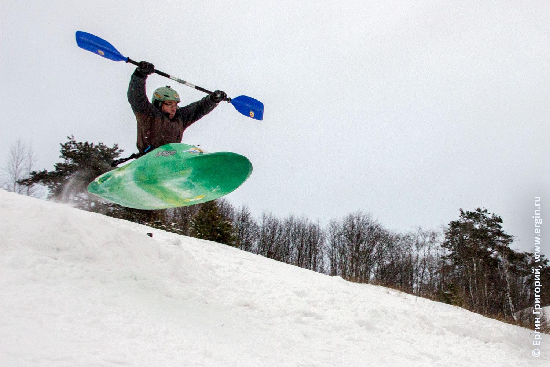 Каяк летит по воздуху зимой над заснеженной горой сноукаякинг