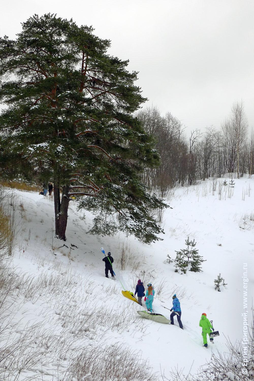 Сноукаякеры с каяками забираются зимой в гору кататься