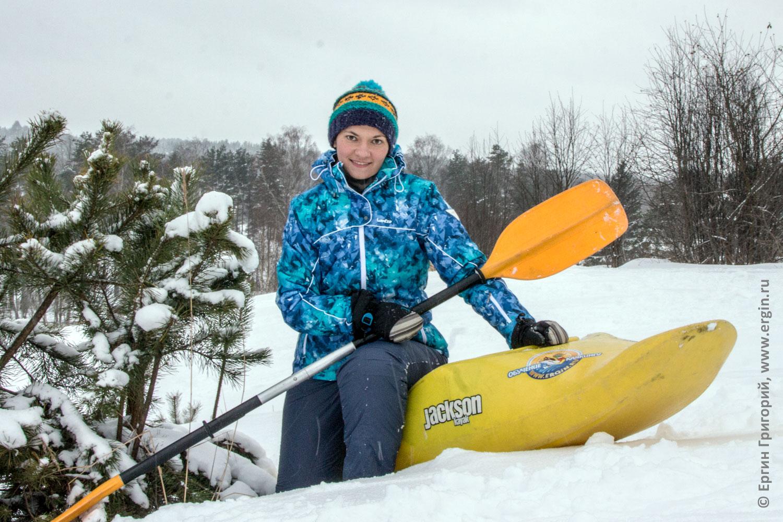 Зимняя девушка каякер с каяком на снегу у елочки