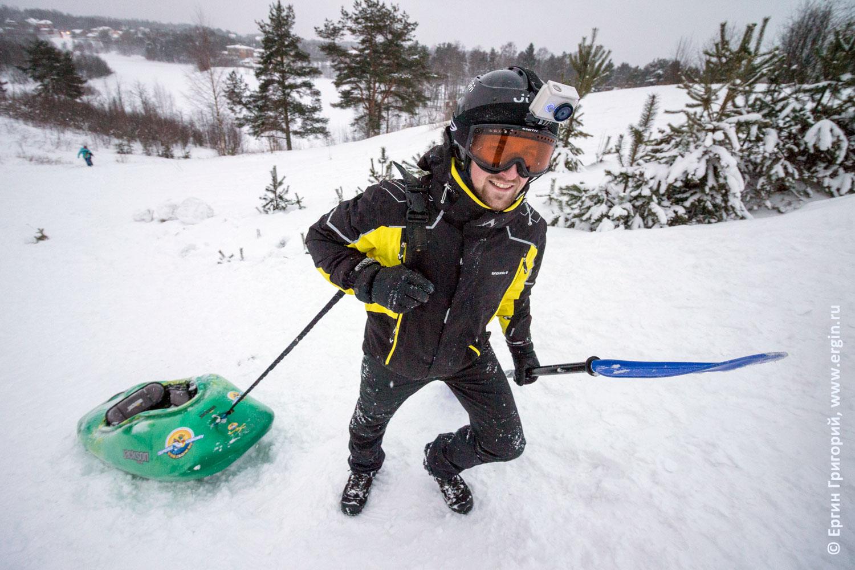 Сноукаякер тащит каяк на привязи по снегу в гору