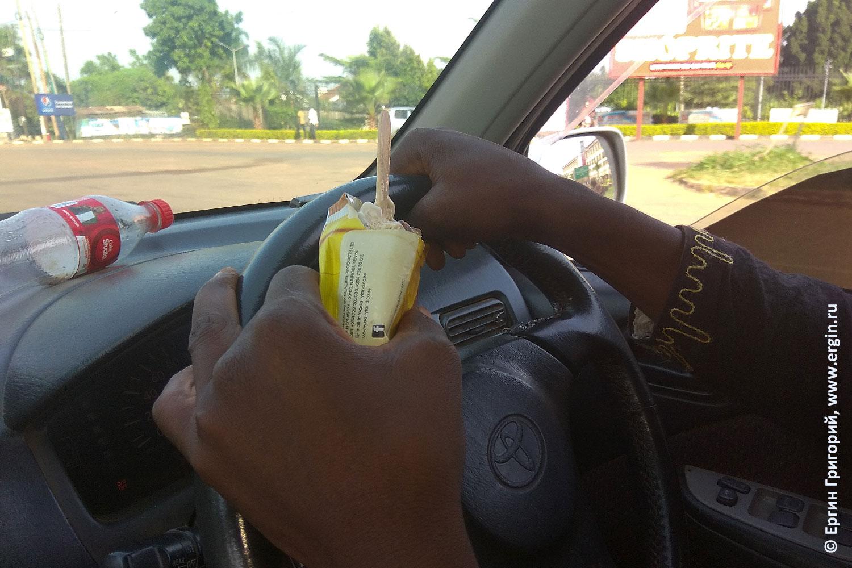 Негр водитель в Уганде ест мороженое с палочки