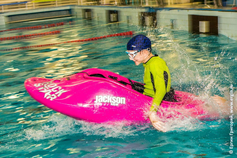 Быстро плывет в бассейне каякер ребенок на каяке