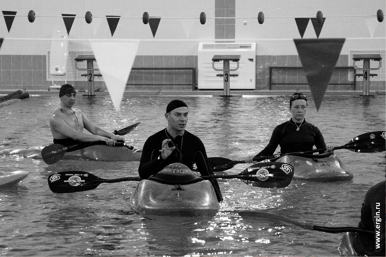 Каякеры в бассейне ранним утром тренируются на каяках с веслами