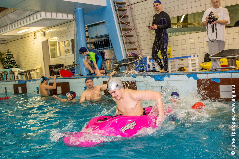 Дети быстро плывут соревнуются в бассейне на каяках