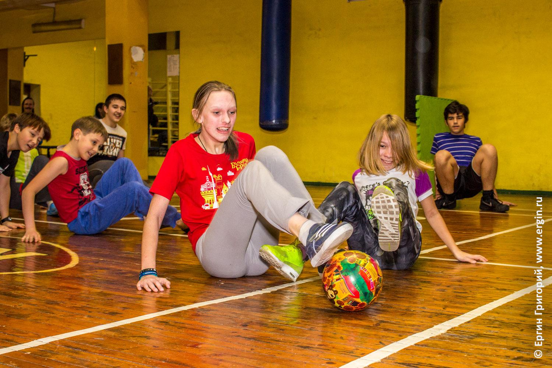 Разминка детей в спортивном зале на четвереньках с мячем