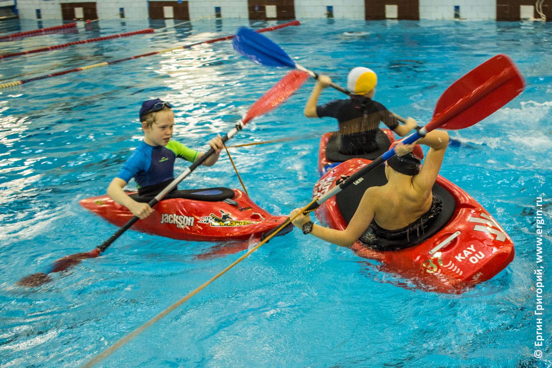 Дети тянут канат на каяках каякеры в бассейне тренировка