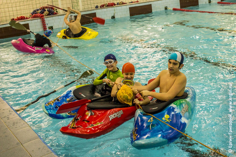 Каякеры дети перетягивают канат в бассейне на каякеах