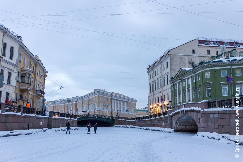 Люди гуляют по льду замерзшей реки Мойки в Санкт-Петербурге вечером