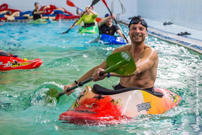 Каякер гребет веслом на каяке в бассейне и улыбается довольный позитивный