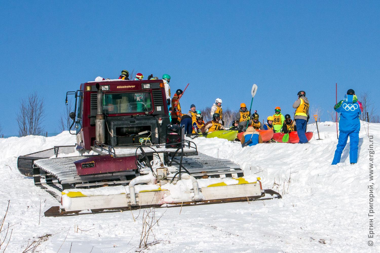 Сноукаякеры на каяках возле ратрака на горнолыжной трассе перед соревнованиями по сноукаякингу