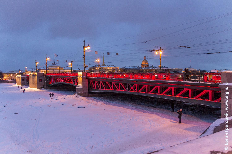 Санкт-Петербург Нева Дворцовый мост и его красная подсветка зимой надо льдом