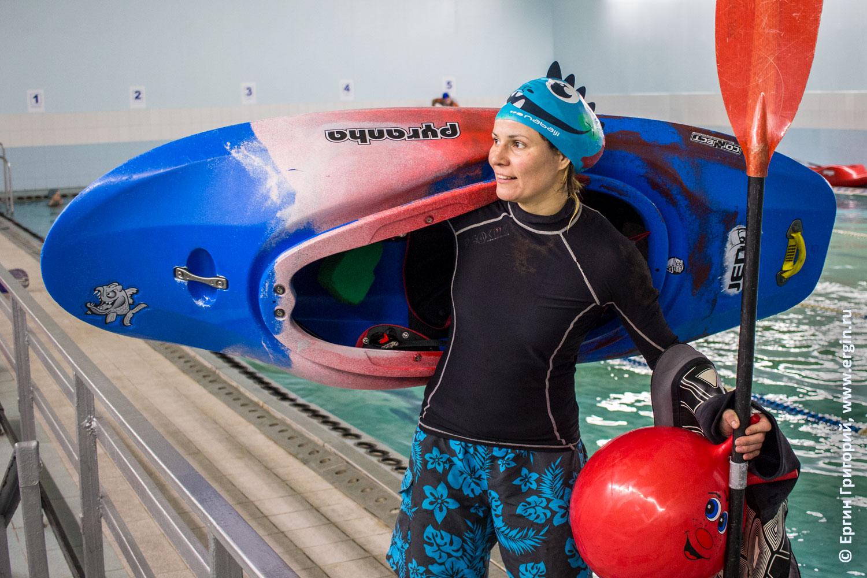 Каякер девушка стоит с веслом и каяком на бортике бассейна