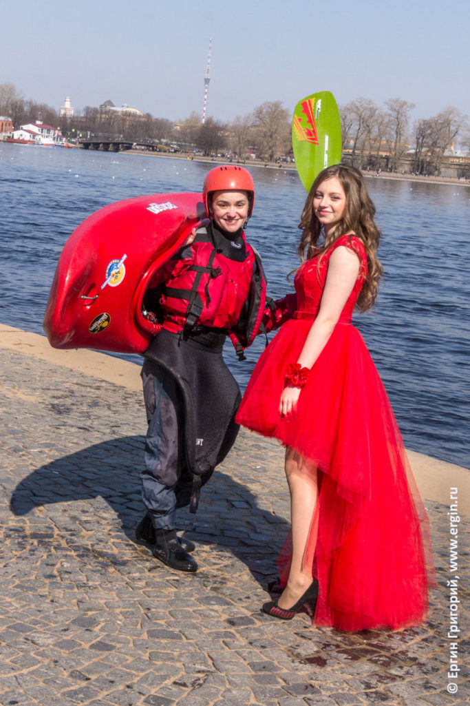В красном платье девушка и каякер с красным каяком и снаряжением