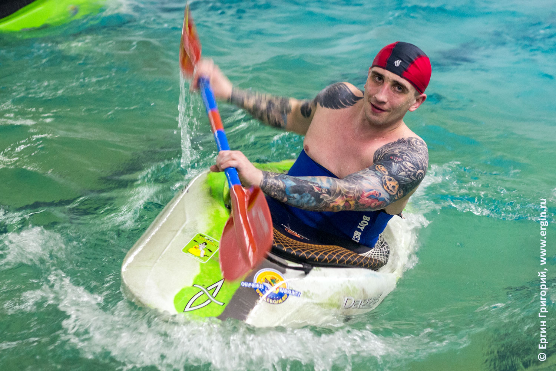 Гребет на каяке веслом в бассейне татуированный каякер