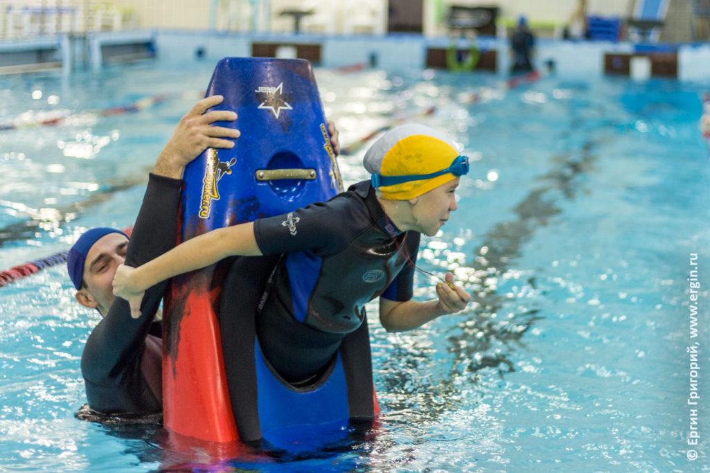 Девочка учится делать носовую свечку на каяке в бассейне