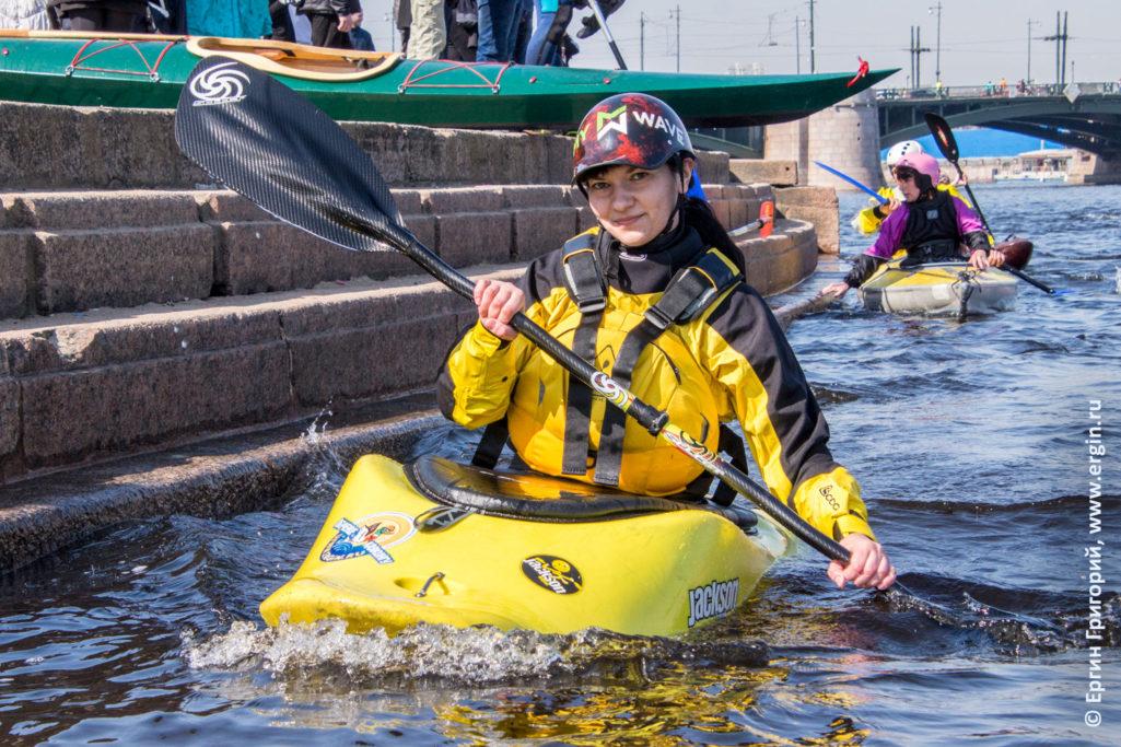 На каяке гребет девушка с веслом