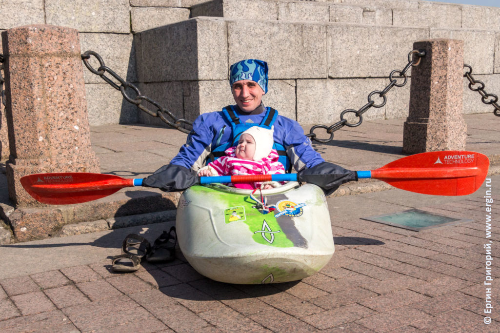 У Ростральной колонный в Санкт-Петербурге каякер с ребенком в каяке перед прогулкой по реке Неве
