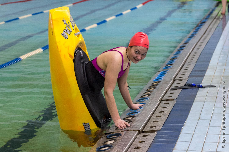 Девушка стоит на носу каяка в бассейне у бортика учится каякингу