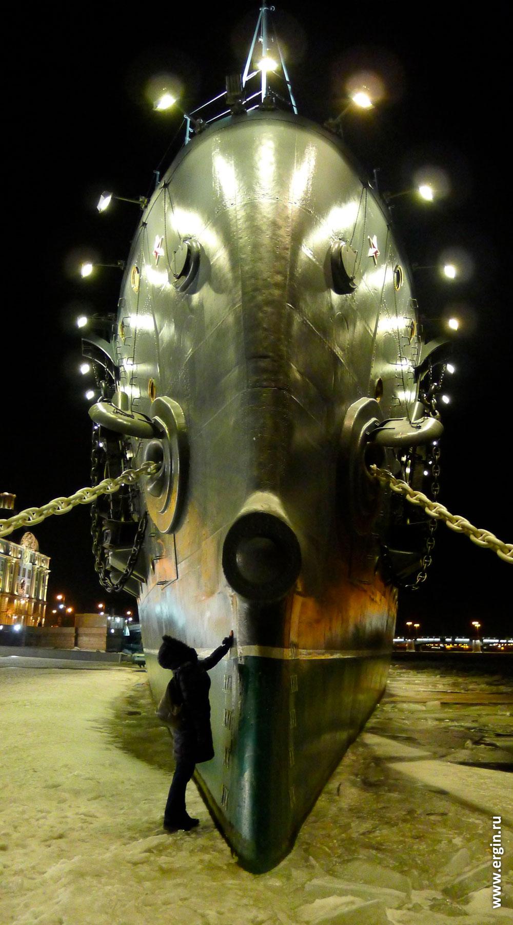 """Стоящий во льдах крейсер """"Аврора"""" в Санкт-Петербурге и люди, трогающие корабль за нос"""