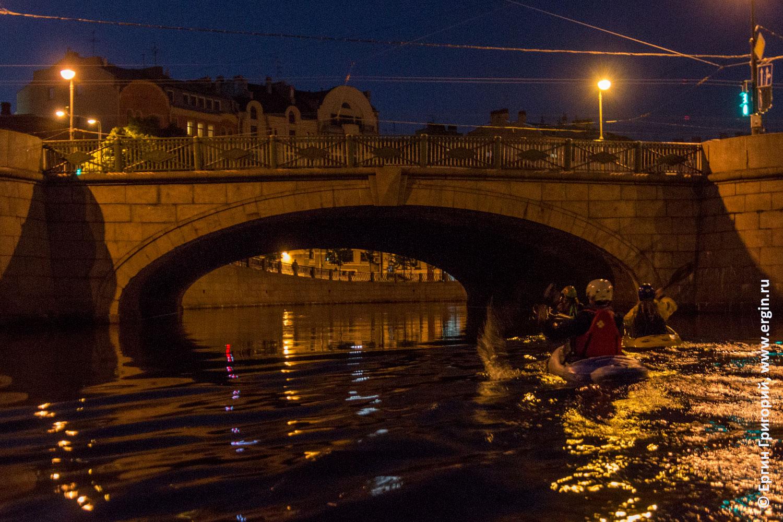 Каякеры идут под Силиным мостов в Санкт-Петербурге по реке Карповке