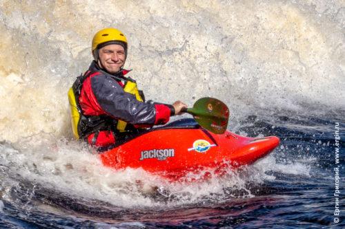 Довольный позитивный улыбающийся каякер фристайлер сидит в пороге на валу катается на каяке