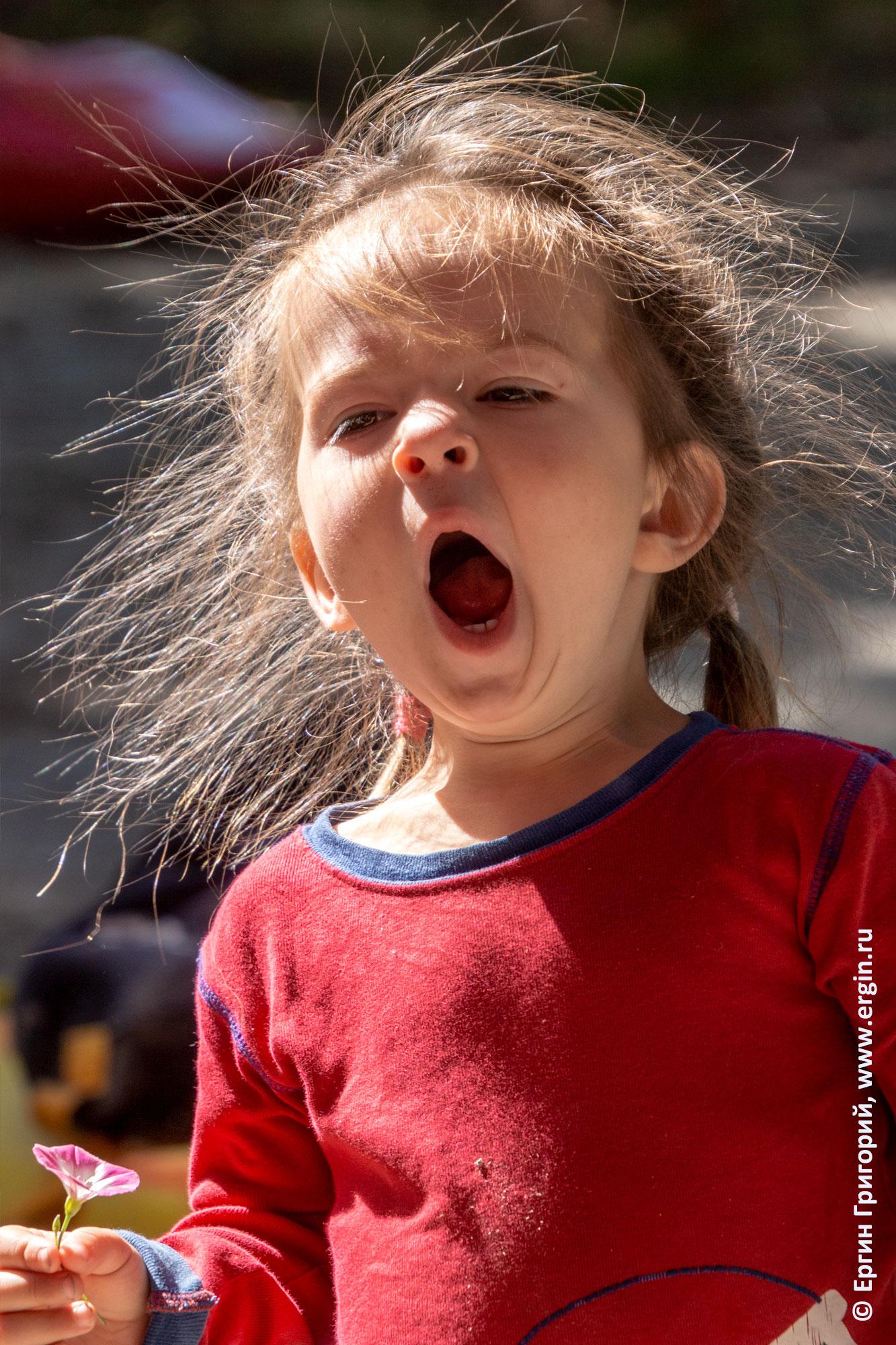 Девочка с цветочком широко зевает. Алтай, родео-тур.