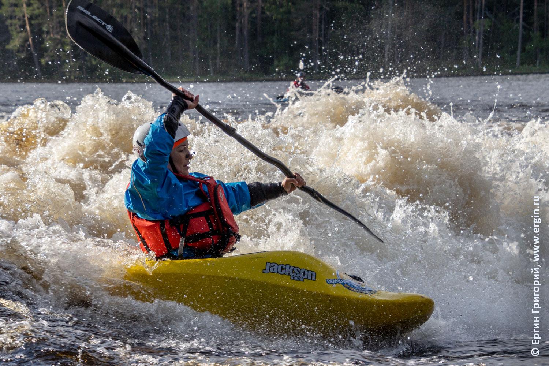 Каякер катается с гордо поднятым веслом на каяке