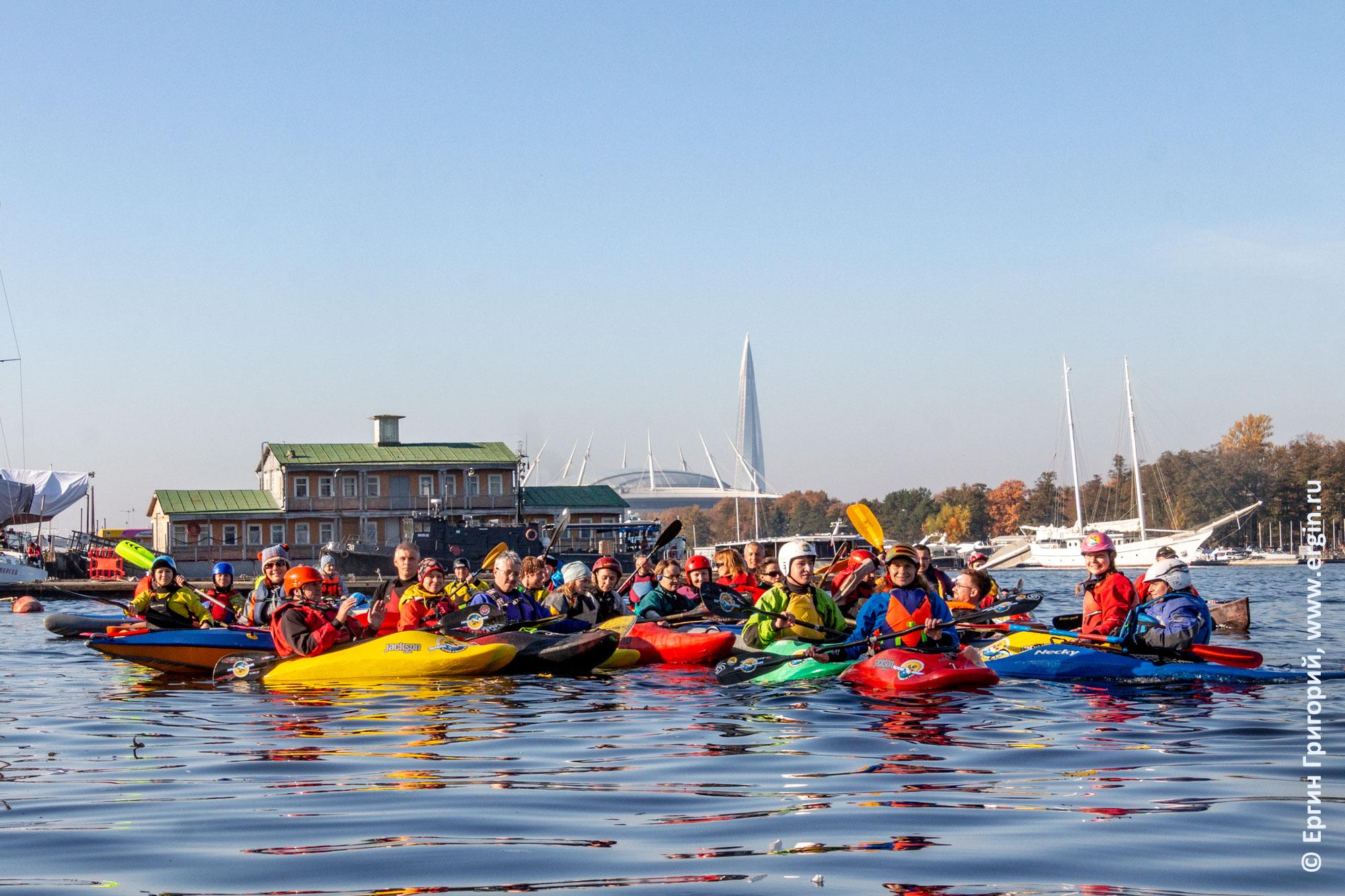 Каякеры с каяками и веслами на воде на фоне башни Газпрома и стадиона Санкт-Петербург