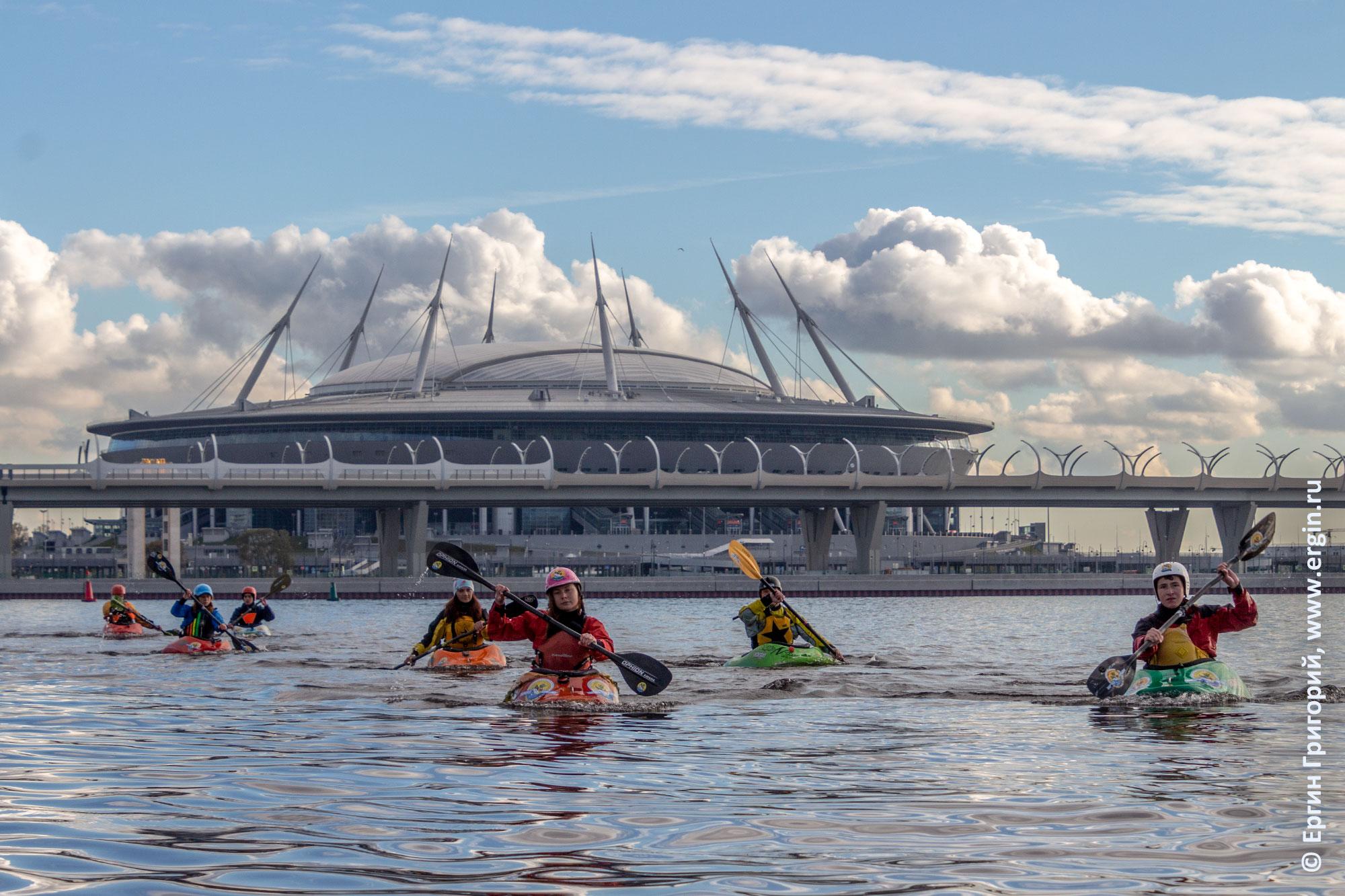 По Невской губе на каяках идут каякеры сзади стадион Санкт-Петербург и ЗСД