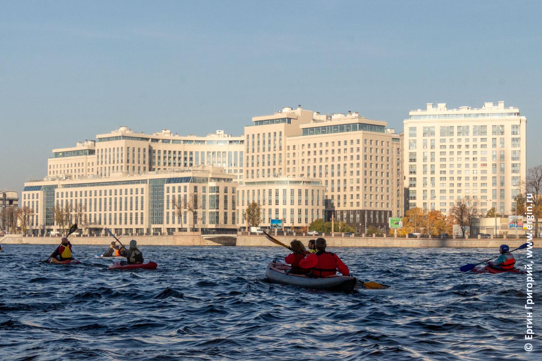 Каякеры Санкт-Петербурге идут мимо больших жилищных комплексов по Невке