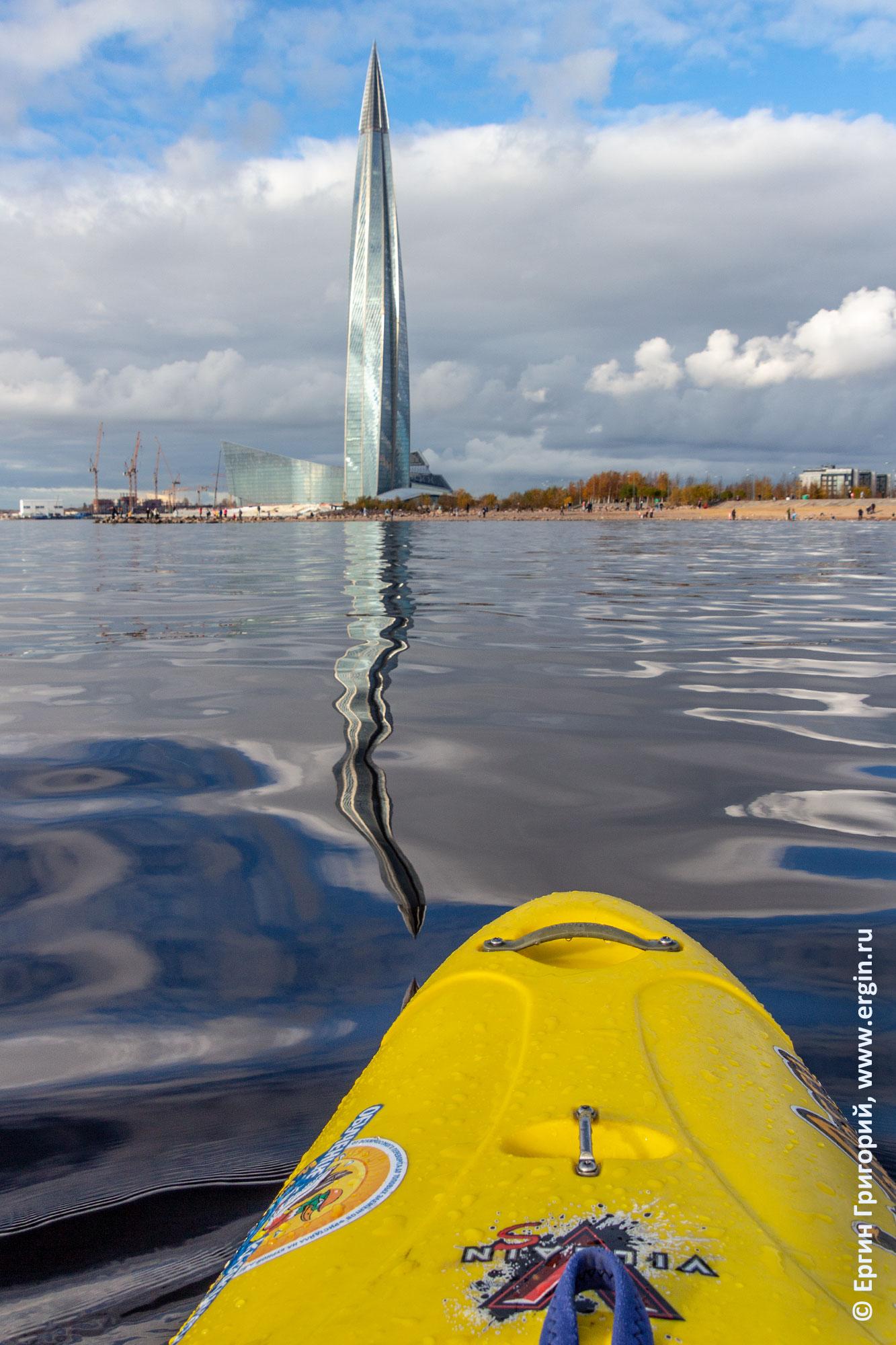 Нос каяка Невская губа в воде криво отражается башня Газпрома