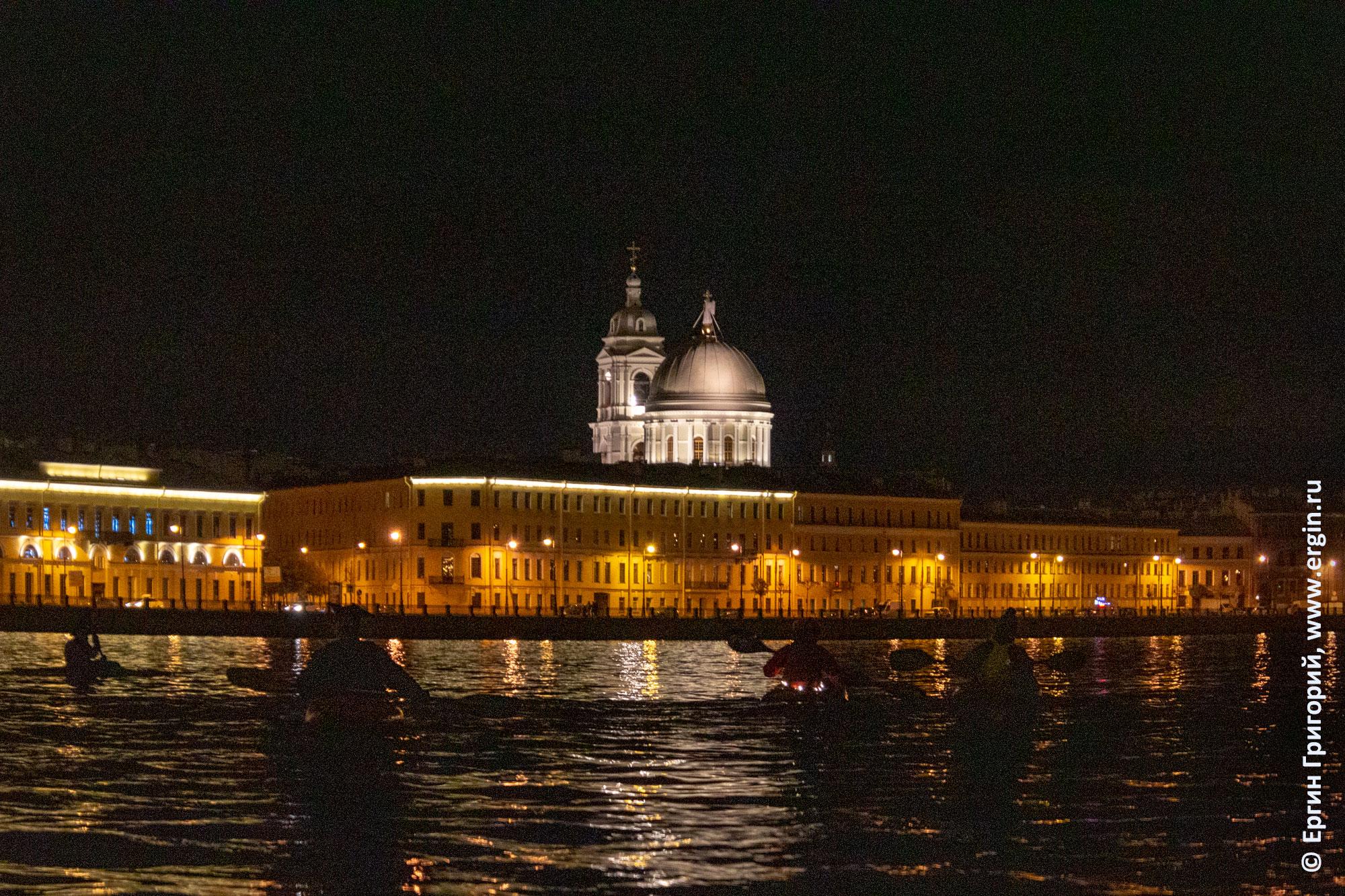 Каякеры идут ночью по Неве мимо церкви святой Екатерины